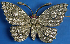 Late Victorian diamond set butterfly brooch the thorax with round cut diamonds the eyes with rubies. The wings are set with four principal round cut diamonds and with graduated cut diamonds of mixed sizes. All in gold faced with silver.PROVENANCE: Th