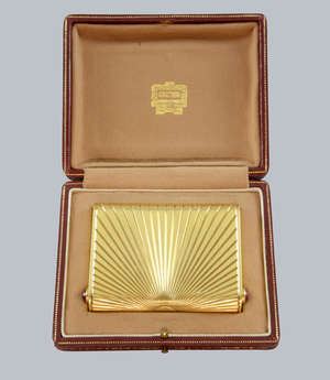 Cartier 18ct gold cigarette case, with fluted sunburst decoration, each push button set with cabochon cut rubies. Hallmarked 1953 and Makers mark JC, Cartier London.  Boxed.