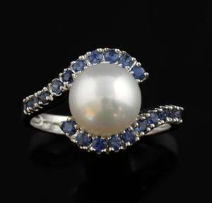 Contemporary ring set with single cultured pearl and two curved lines of sapphire in white gold.  Ring size - N