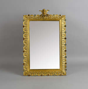 Cast gilt metal mirror surmounted by a cherub and with a border of paste set sunflowers and leaves. 42 x 28 cm
