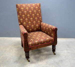 19th century mahogany framed and upholstered armchair on carved supports, reeded turned legs and castors