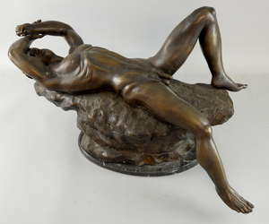 20th century  cast metal study of a naked man reclining on rocks