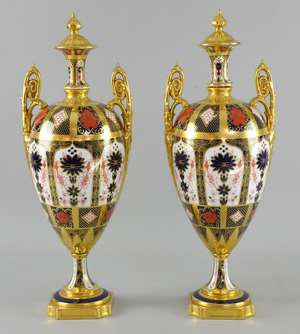 Pair of Royal Crown Derby two handled vases and covers decorated in the Imari palette with flowers and foliage, on shaped bases, 42cm high, (tops damaged prior to entry for auction),