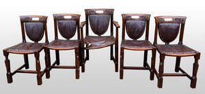 Five  chairs in Arts and Crafts manner, curved backs with pierced and carved detail, shield back and seat upholstered in brown leather with stud fastening, carved square section legs