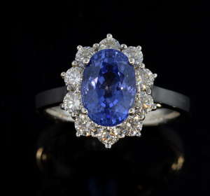Sapphire and diamond cluster ring, the centre oval cut sapphire weighing approximately 3.32 carats within a surround of ten round brilliant cut diamonds. Estimated total diamond weight 0.90 carats. Mounted in 18 ct white gold,  ring size - M
