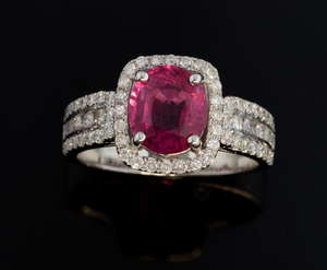 Ruby and diamond halo dress ring. set with a 2.29 carats oval cut ruby within a pave set diamond surround and diamond set shoulders. Mounted in 18 ct white gold, total diamond weight 0.60 carats.  Ring size - N 1/2 Ruby certificated as natural, no he