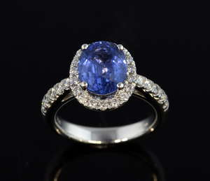 Sapphire and diamond dress ring, oval cut sapphire to the centre with a border of round brilliant cut diamonds, further diamonds set to the shoulders and underneath the sapphire, mounted in 18ct white gold. Sapphire weight 3.64 carats.  Ring size - M