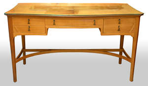 Edward Barnsley, 1900-1987, walnut serpentine fronted desk with central drawer flanked by two drawers to each side  76cm h  x 133cm w  x 50cm d   wide and an Edward Barnsley walnut arm chair with cane seat, both stamped Barnsley
