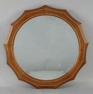 Edward Barnsley walnut  wall mirror of shaped circular form with blond wood stringing,  40cm diameter.