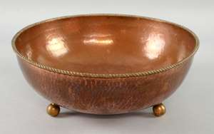 Dryad, Leicester, an Arts and Crafts copper bowl, planished finish, rope twist rim, raised on three ball feet, stamped marks 28.5 cm diameter
