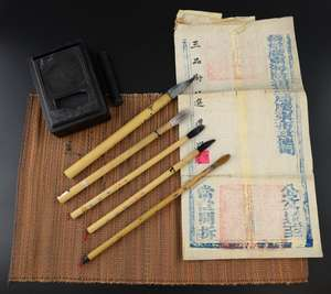 Five Chinese bamboo handled brushes, print role, pallet in hard wood case and three pieces of printed calligraphy,