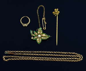 Green enamel and seed pearl brooch, in 18 ct gold, the reverse inscribed Millie1901-1917, a 9 ct gold chain, ring charm and unmarked clover leaf stick