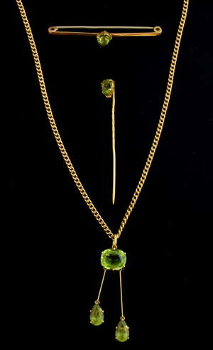 Early 20th C negligee pendant, set with three peridot, largest 10.5 x 8.7 mm, unmarked gold, pendant length 4 cm, on a 15 ct gold chain, similar stick pin and bar brooch