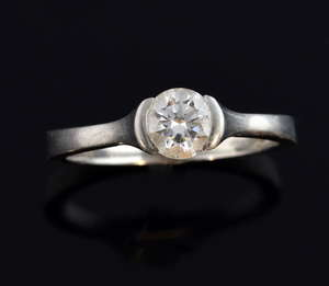Solitaire diamond ring set in platinum tension setting, stone of 0.62 carat, with accompanying GIA certificate, colour grade G , clarity Si2.  Ring size M 1/2