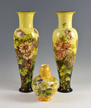 A pair of Royal Doulton faience vases in yellow ground with floral decoration, 43cm, and another similar, 18cm.