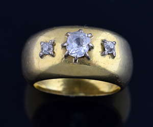 Gold and diamond band ring set with three old cut diamonds in a claw setting mounted in 18ct yellow gold.