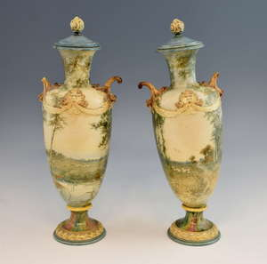 A pair of Royal Doulton vases and covers, decorated with landscape scenes, with swag and mask detail to rim and scrolling handles, 47 cm high (2)