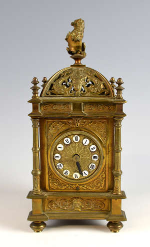 Brass mantel clock, the dial with white enamelled cartouches and Roman numerals, movement by Buren, the pierced dome with rampant lion finial, dolphin and mask decoration on column supports and turned feet, 26cm high,