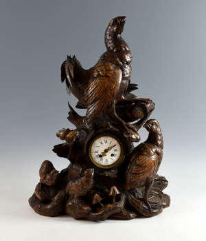 Late 19th century German carved wood Black Forest mantel clock decorated with black grouse, two chicks, oak leaves, and mushrooms, the clock face with enamel and blue painted Roman numerals, eight day movement, 63cm high