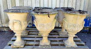 Set of six composition stone urns of campana form on pedestal bases, 65cm high