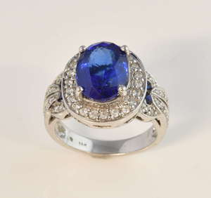 Tanzanite and diamond dress ring, oval cut tanzanite, estimated weight 4.97carat, surrounded by round brilliant cut diamonds, mounted in white metal stamped14ct, ring size M,