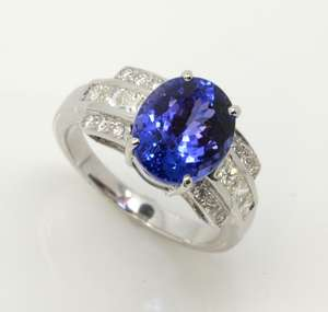 Tanzanite and diamond dress ring, oval cut tanzanite estimated weight 5.18 carats, princess cut and round cut diamonds set in shoulders, estimated total diamond weight 0.64 carat, mounted in white metal stamped 14 ct, ring size P